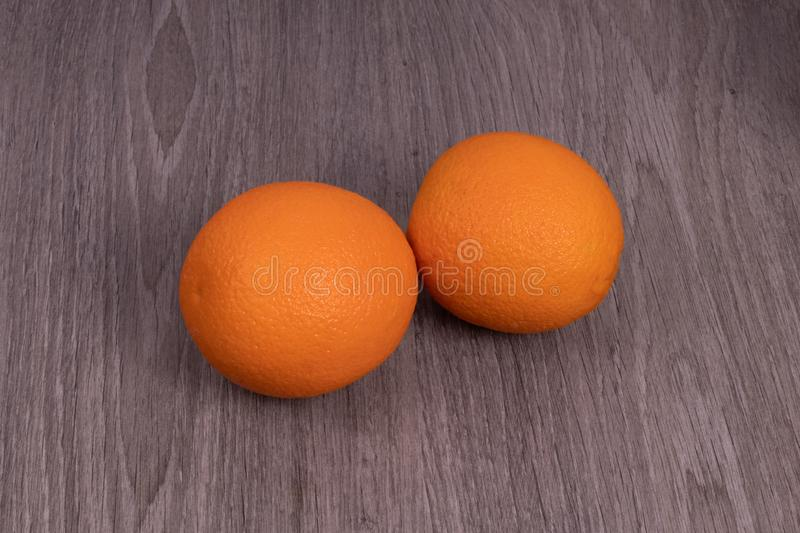 Two oranges located side by side with a wood structure.  royalty free stock photos
