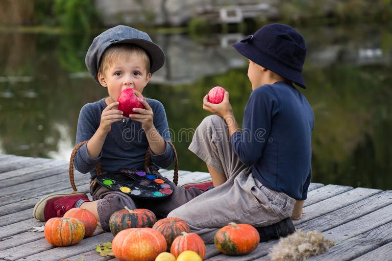 Two ordinary boys paint small apples royalty free stock photo