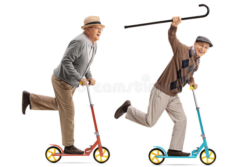 Two overjoyed seniors riding scooters royalty free stock image