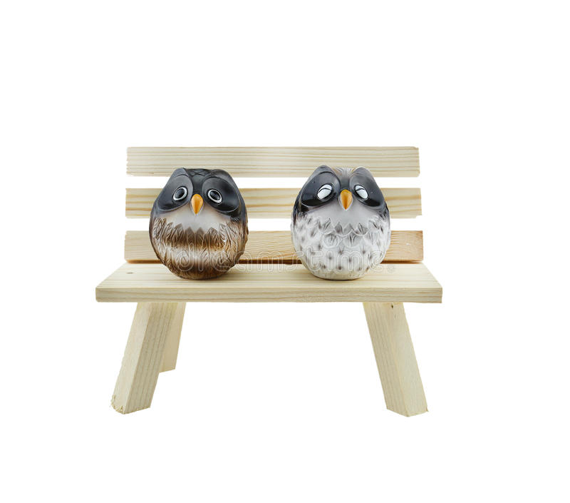 Two Owls on wooden chair. Two Owls on a small wooden chair with white background royalty free stock image