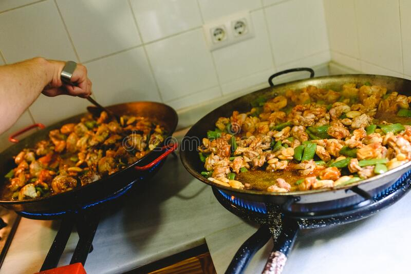 Two paella pan preparing the chicken and the fried vegetables stock images