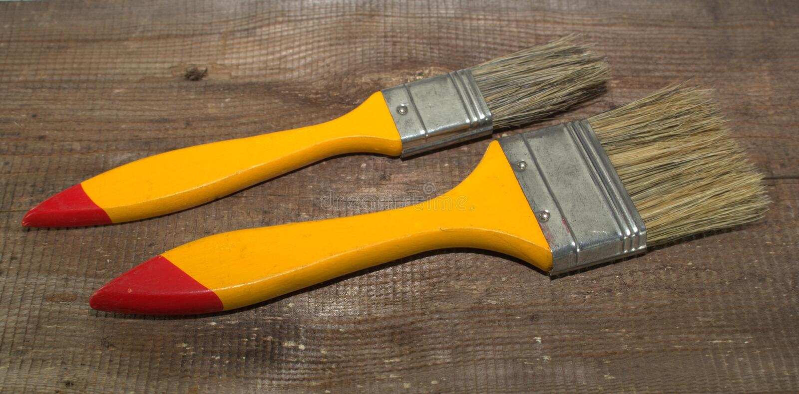 Two paint brushes 1 inch wide and 2 inches wide with yellow handles on a wooden background. Close-up royalty free stock photo