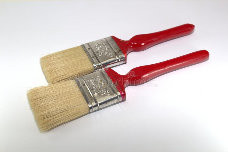 Two paint brushes 2 inches wide with red handles on a wooden background. Close-up royalty free stock photo