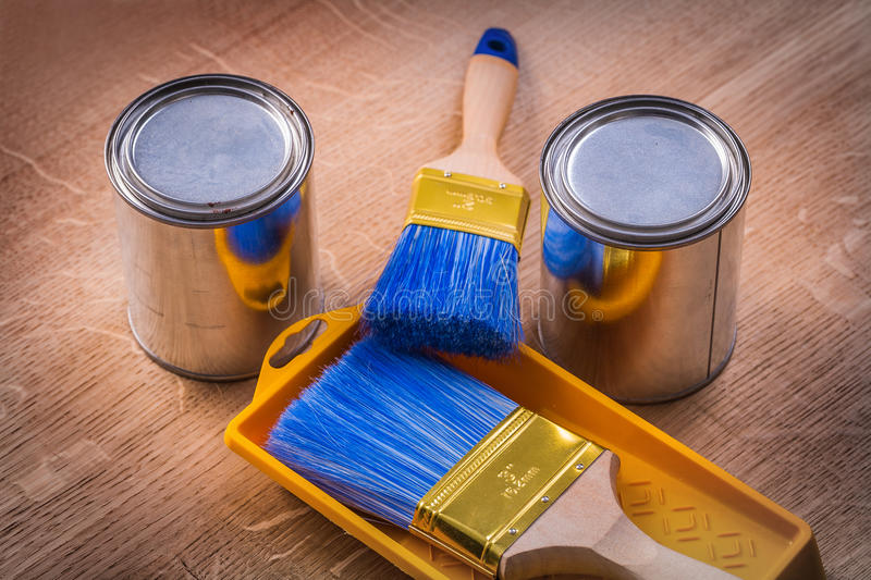 Two paint cans brushes tray on wooden board royalty free stock image