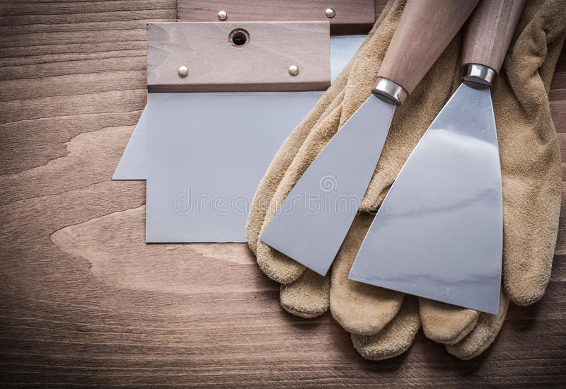 Two paint scrapers putty knifes working gloves.  stock photography