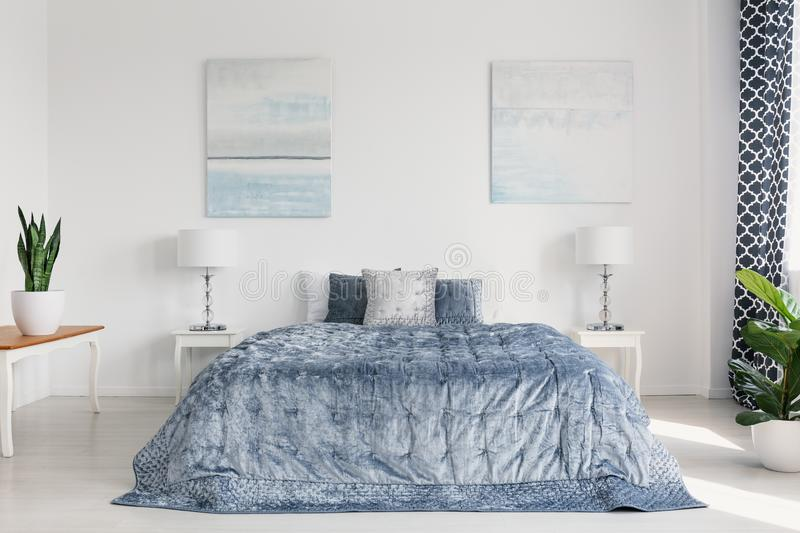 Two painting on the wall of elegant bright bedroom interior with cozy bedding and white furniture. Concept stock image