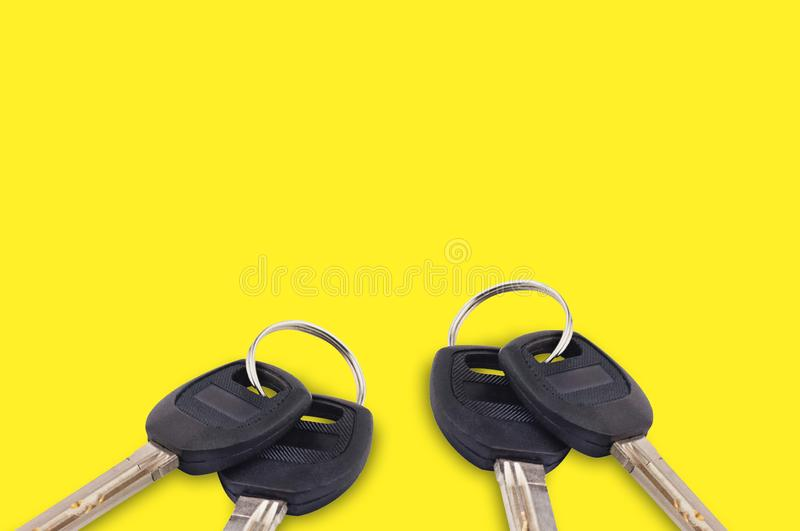 Two pair of metal shiny keys with black plastic or rubber handle attached of keyring for door or car on yellow background with cop stock photography