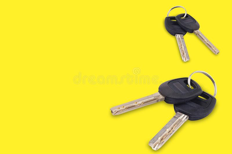 Two pair of metal shiny keys with black plastic or rubber handle attached of keyring for door or car on yellow background with cop royalty free stock photography