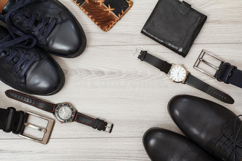 Two pairs of black leather men\'s shoes, belts for men, wallets and watches on gray background royalty free stock photography
