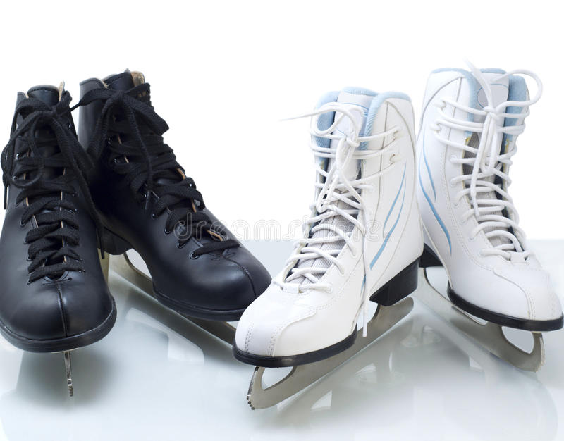 Two pairs of black and white figure skates stock image