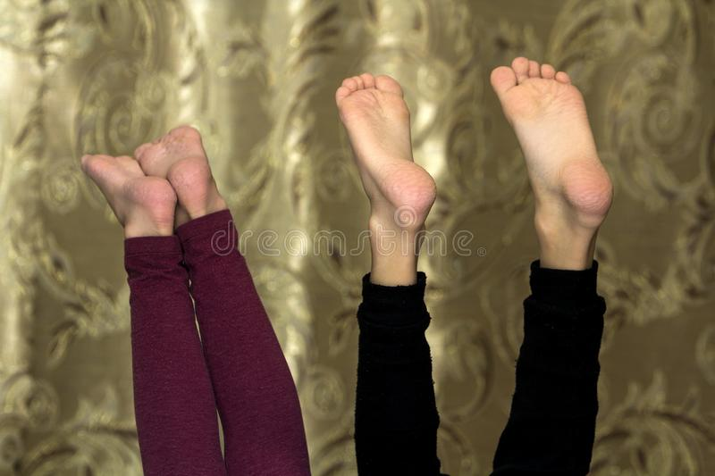 Two pairs of children bare teet sticking up royalty free stock images