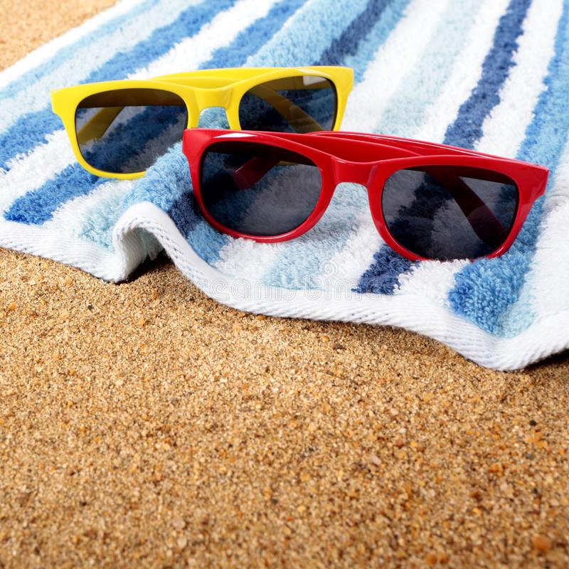 Two pairs couple sunglasses beach towel sand background royalty free stock photo
