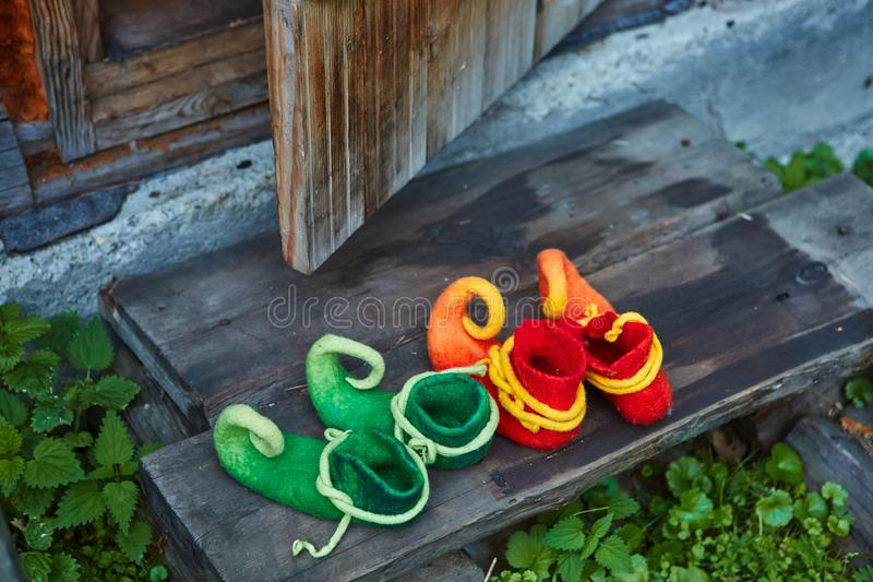 Two pairs of dwarf felt shoes at the entrance of an old wooden house. Dwarves came to visit.  royalty free stock images