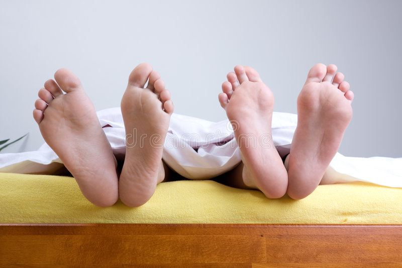 Download Two pairs of feet in bed stock photo. Image of heels, human - 7638402