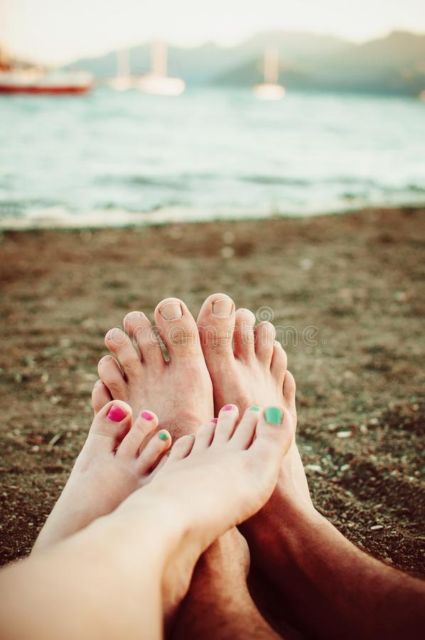 Two pairs of feet, male and female crossed on sea stock photos