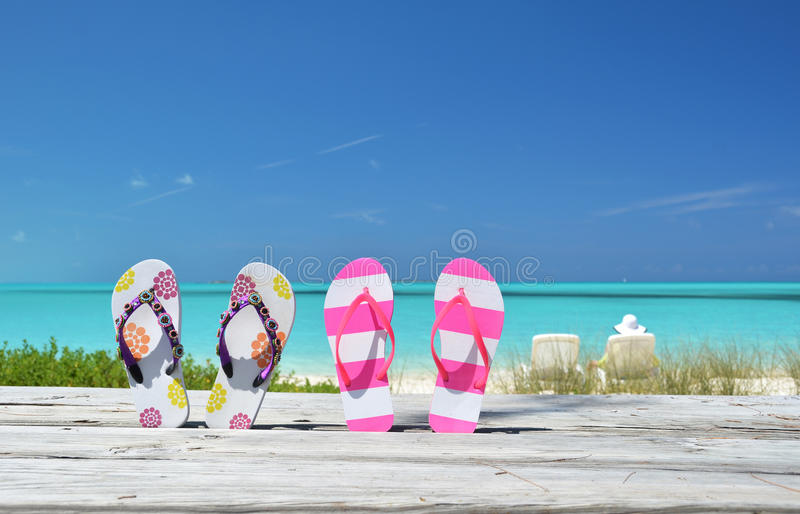 Two pairs of flip-flops. Against ocean. Exuma, Bahamas stock photography