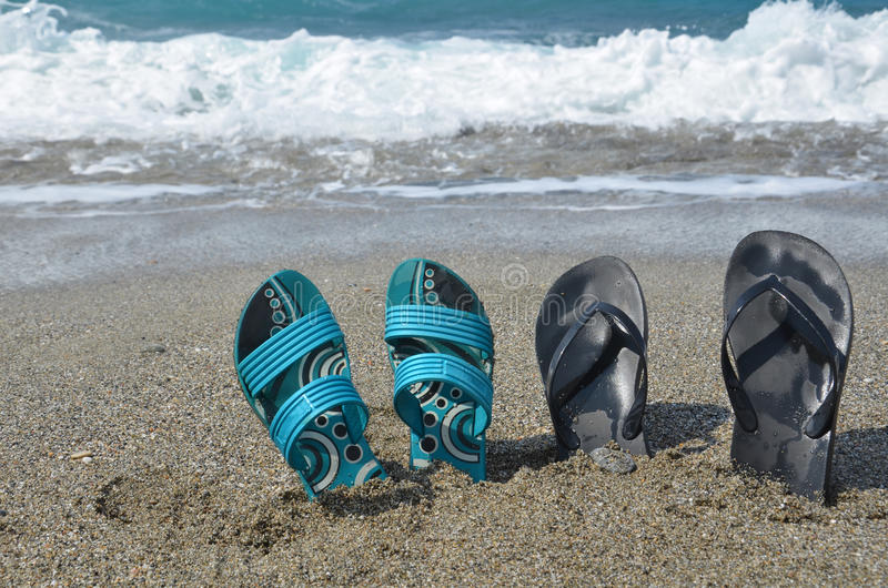 Two pairs of flip-flops on the beach, tropical vacation concept stock photo