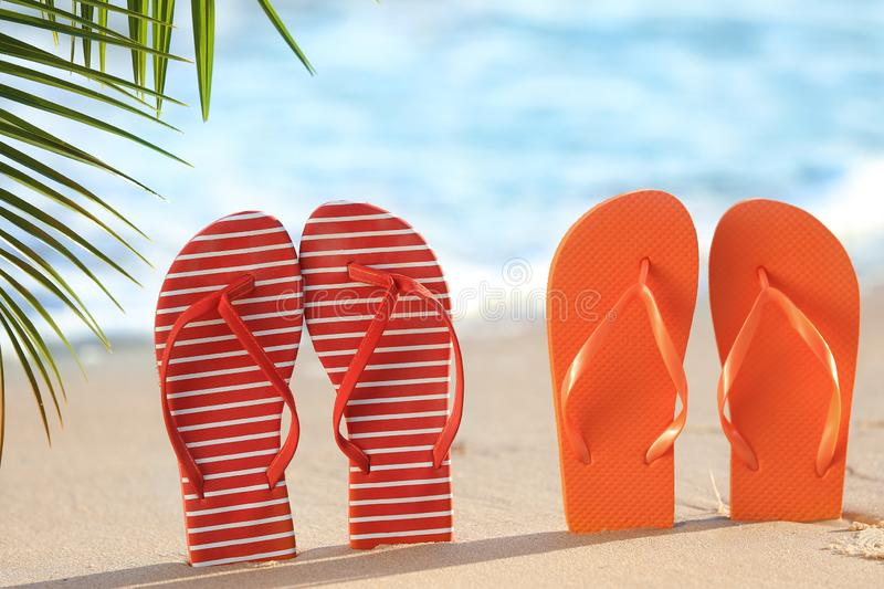 Two pairs of flip-flops on sea beach at tropical resort royalty free stock photography