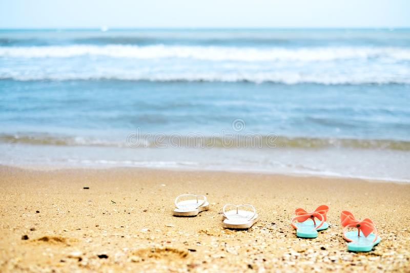 Two pairs flip flops on the beach stock photos