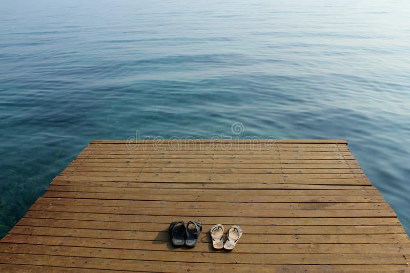 Two pairs of flip-flops on wooden deck near seashore royalty free stock photo