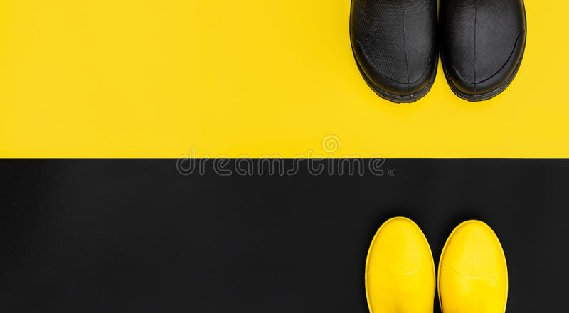 Two pairs of gumboots - yellow female and black male - standing opposite to each other on the inverse backgrounds. stock photo