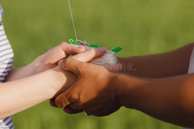 Two pairs hands. Male tanned and white female. Keep spool of thread from kite. Bright green background. royalty free stock photo