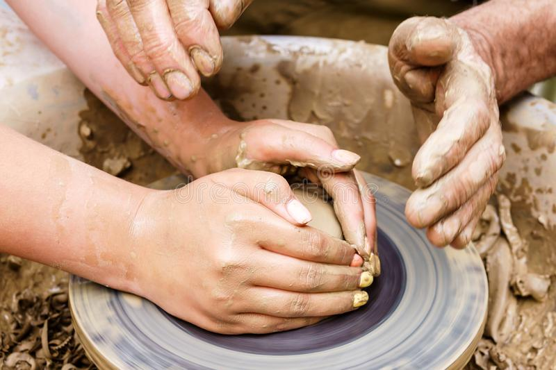 Two pairs of hands mold something from clay on a potter`s wheel stock image