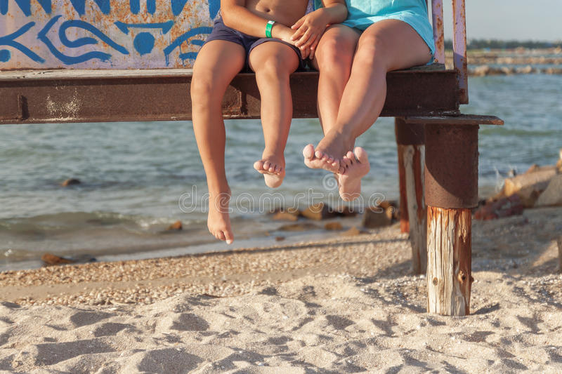 Two pairs of legs dangling over the beach sand.  stock image
