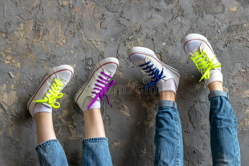 Two pairs of legs of a girl and a young man wearing blue jeans and white sneakers, feet up on a vintage textured background wall, royalty free stock image