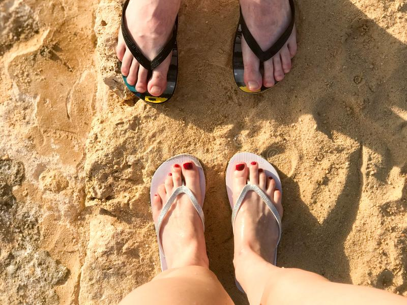 Two pairs of legs male and female with a beautiful pedicure in black and white flip-flops on the sea in a tropical resort on sand royalty free stock photo