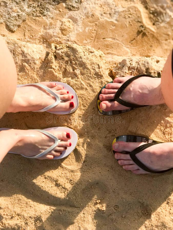Two pairs of legs male and female with a beautiful pedicure in spanking on the sea in a tropical resort on the sand on the beach a stock photography