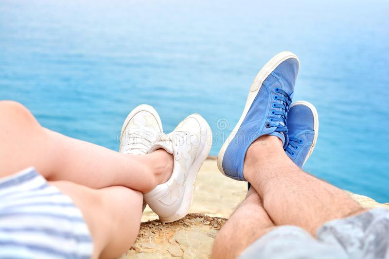 Two pairs of legs, male  and female,  first person view. Tourists resting on a rock against the background of the sea stock photo