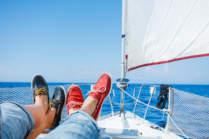 Two pairs legs in red and blue topsiders on white yacht deck. Yachting stock image