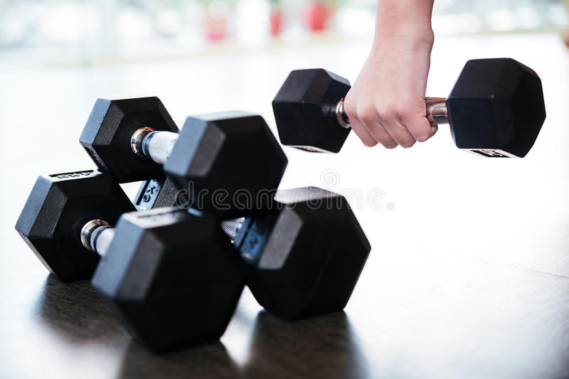 Two pairs of metal dumbbells on the floor. Used by young sportswoman royalty free stock photo