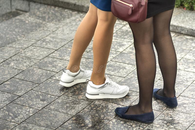 Two pairs of slim girls legs in short skirts, white leather sneakers and comfortable summer shoes on low platform. Fashion, style stock photos