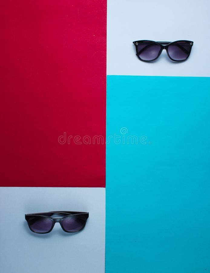 Two pairs of sunglasses on a colored paper background stock photo
