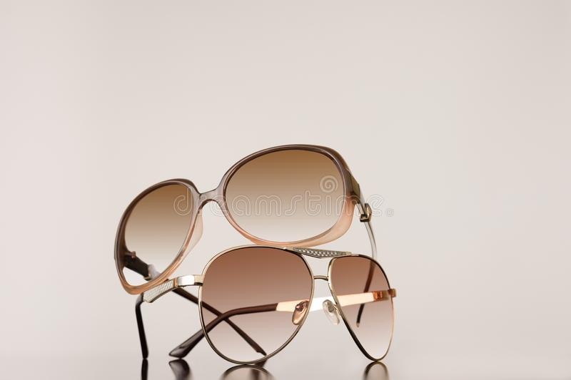 Two pairs of womens sunglasses stacked on top of each other with plain background stock photography