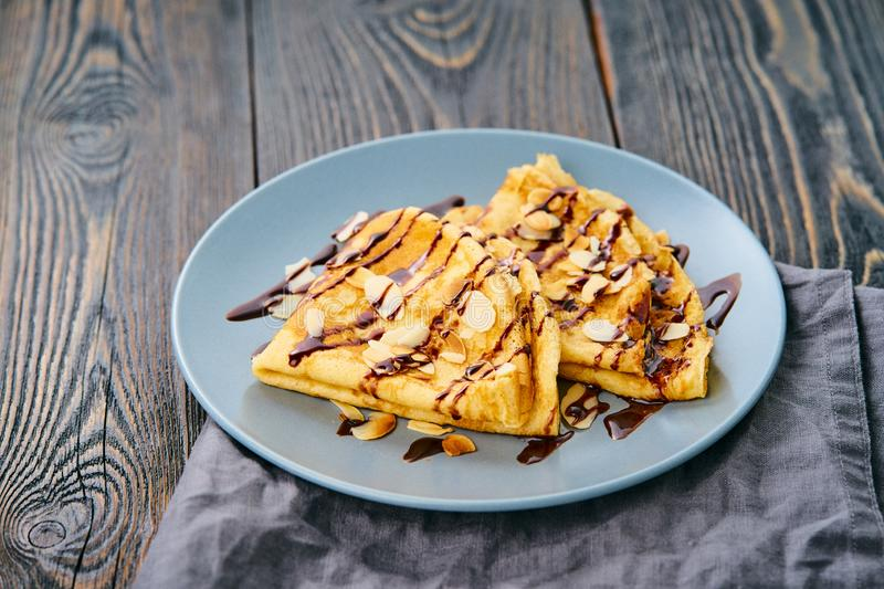 Two pancakes with chocolate syrup, almond flakes on plate, honey flows from spoon, side view.  stock photos