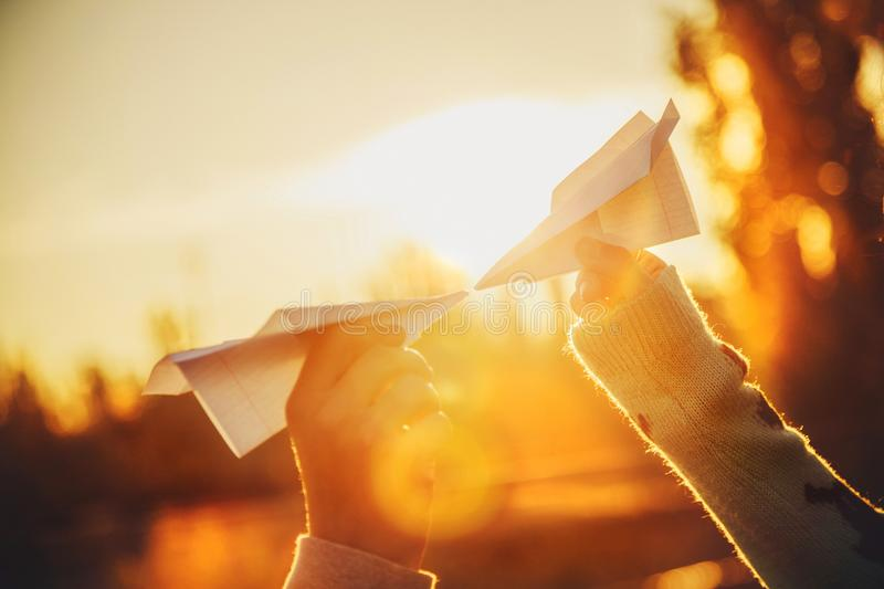 Two paper airplanes in hands looking at each other at sunset. Young people holding paper aeroplanes, love, relations concept stock image