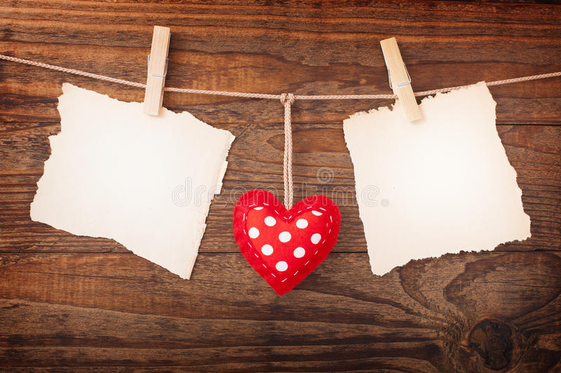 Two paper blank and red heart hanging on wooden background stock photography