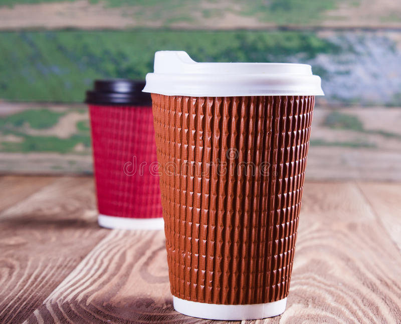Two paper coffee cups. On wood desk royalty free stock photography