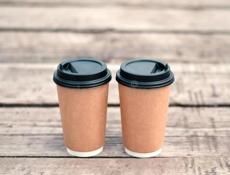 Two paper coffee cups on a wooden surface. Coffee to go. Brown stony royalty free stock photos