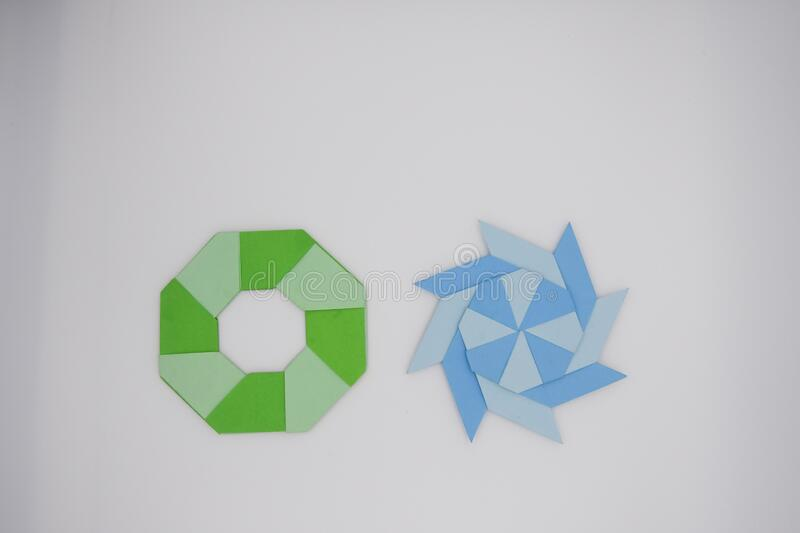 8 pointed ninja star paper fold. Two paper fold of 8 pointed ninja star green and blue were taken stock image