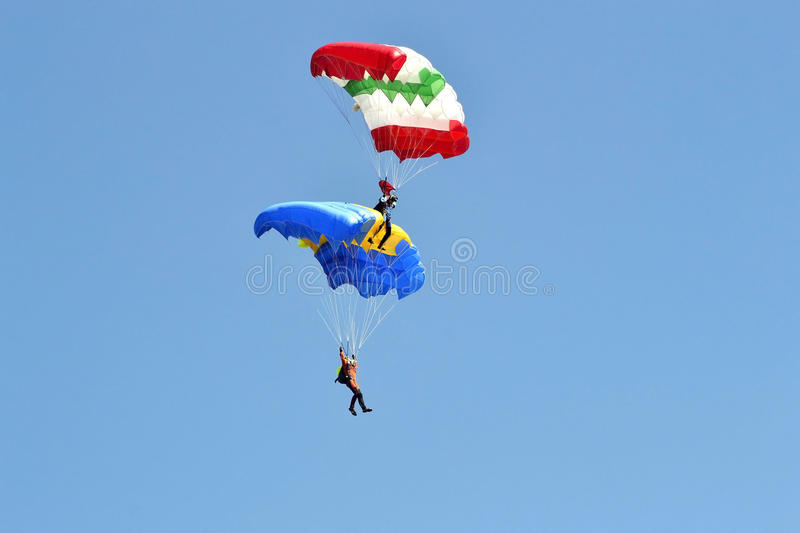 Two parachutists with multi-colored parachutes fly in the sky. royalty free stock photos