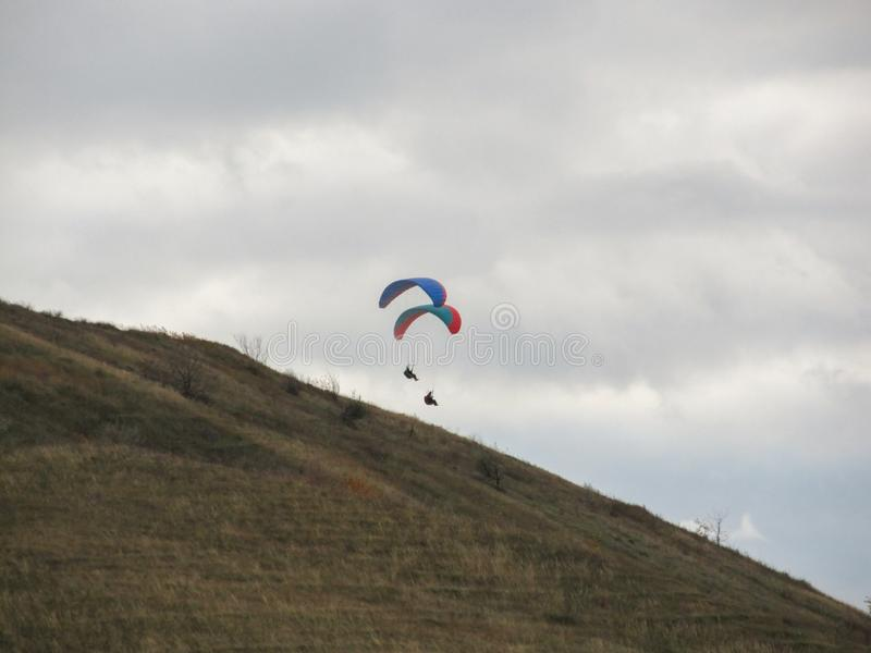 Two paragliders floating in the air above a high mountain royalty free stock photo