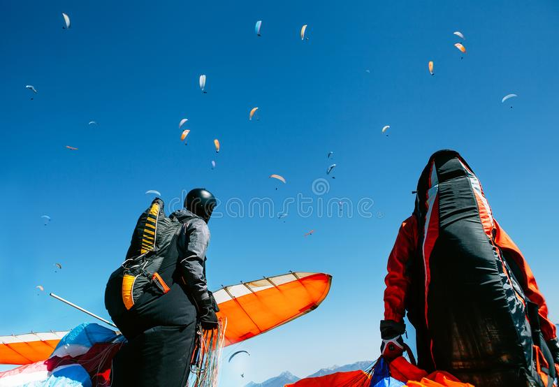 Two paragliders with full flight equipment look on soaring another paragliders in sky stock images