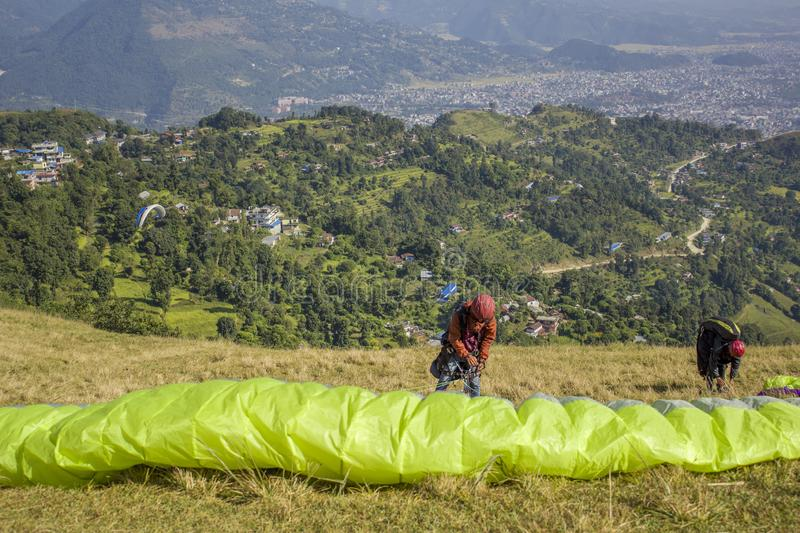 Two paragliders prepare parachutes for takeoff on the hillside against the backdrop of the city in a green mountain valley stock photo