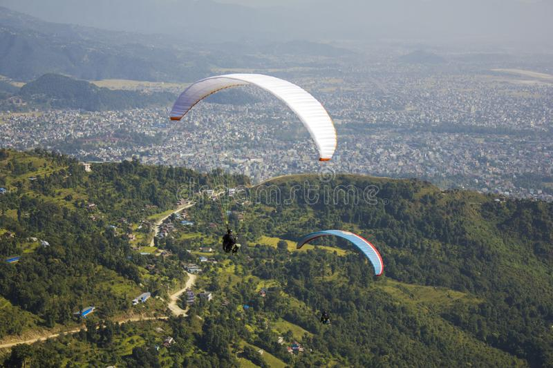 A two paragliders on a white and blue parachute fly over the green mountains a city in the valley royalty free stock images
