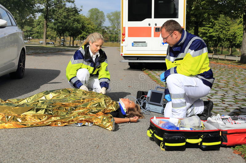 Two paramedics helping a woman after a traffic accident with golden blanket stock photos