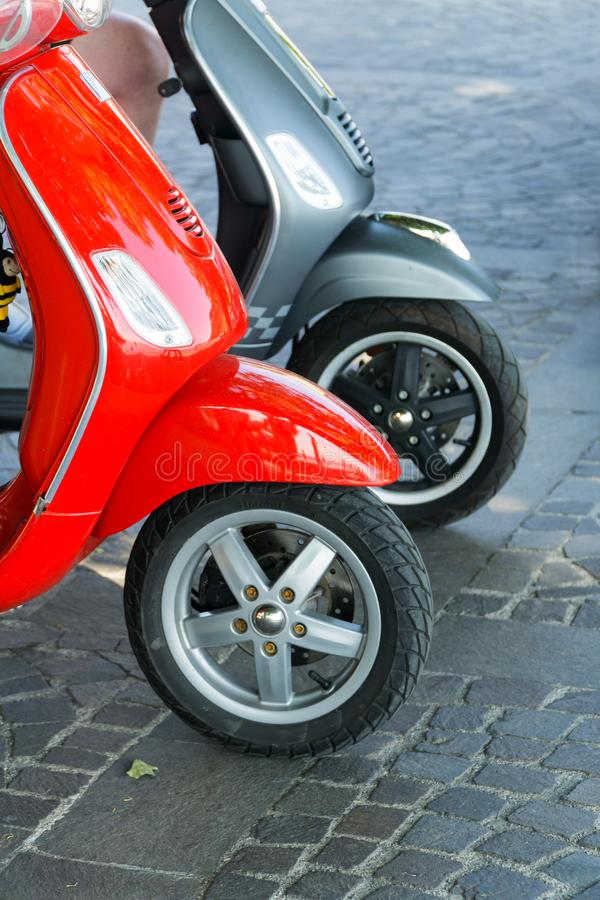 Two parked red and gray scooters on a cobblestone street. royalty free stock images